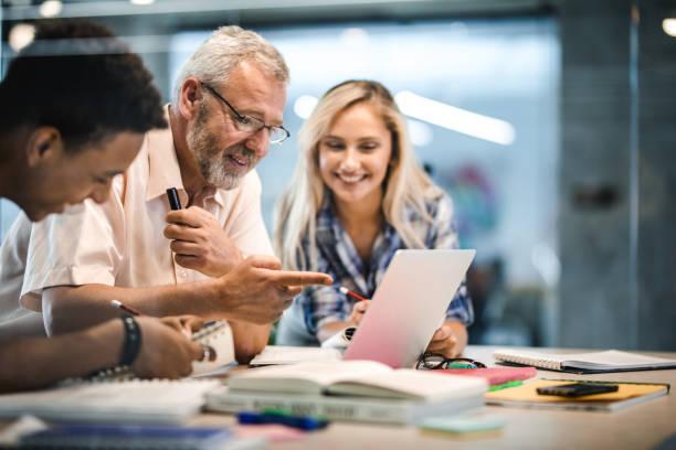 happy mature professor and his students using laptop at campus. - professore foto e immagini stock