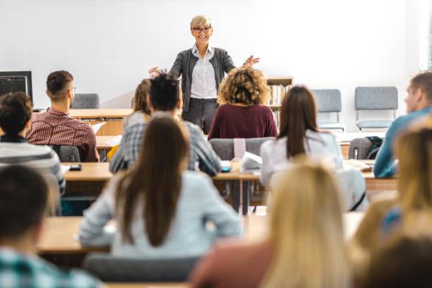 Happy mature professor giving a lecture in front of her students at lecture hall. Happy senior teacher talking to large group of college students in amphitheater. lecture hall stock pictures, royalty-free photos & images