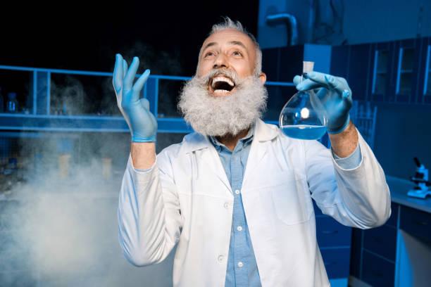glücklich reife wissenschaftler im laborkittel hält kolben mit reagenzien im labor - versuche nicht zu lachen stock-fotos und bilder