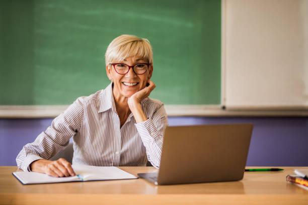 happy mature teacher at the desk in the classroom. - professore di scuola superiore foto e immagini stock