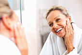 istock Happy mature woman admiring herself in the mirror 121356233