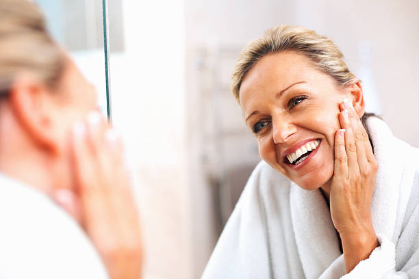 happy mature woman admiring herself in the mirror - huid stockfoto's en -beelden
