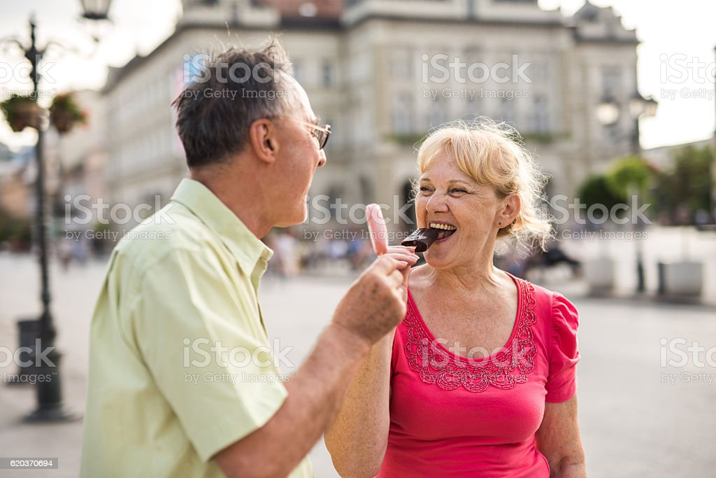 Happy mature woman and her husband enjoying in ice-cream outdoors. zbiór zdjęć royalty-free