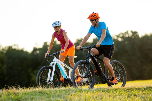 happy mature woman and man cycling together stock photo