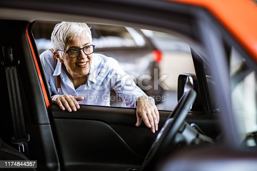 istock Happy mature woman buying a car in a showroom. 1174844357