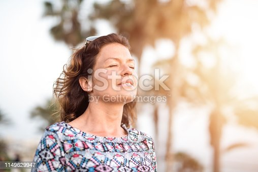 Happy mature woman day dreaming with eyes closed while on a vacation.