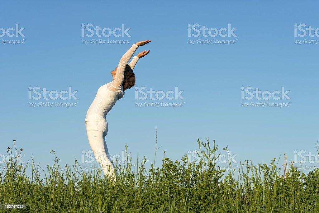 happy mature woman doing yoga exercises outdoors - sun salutation stock photo