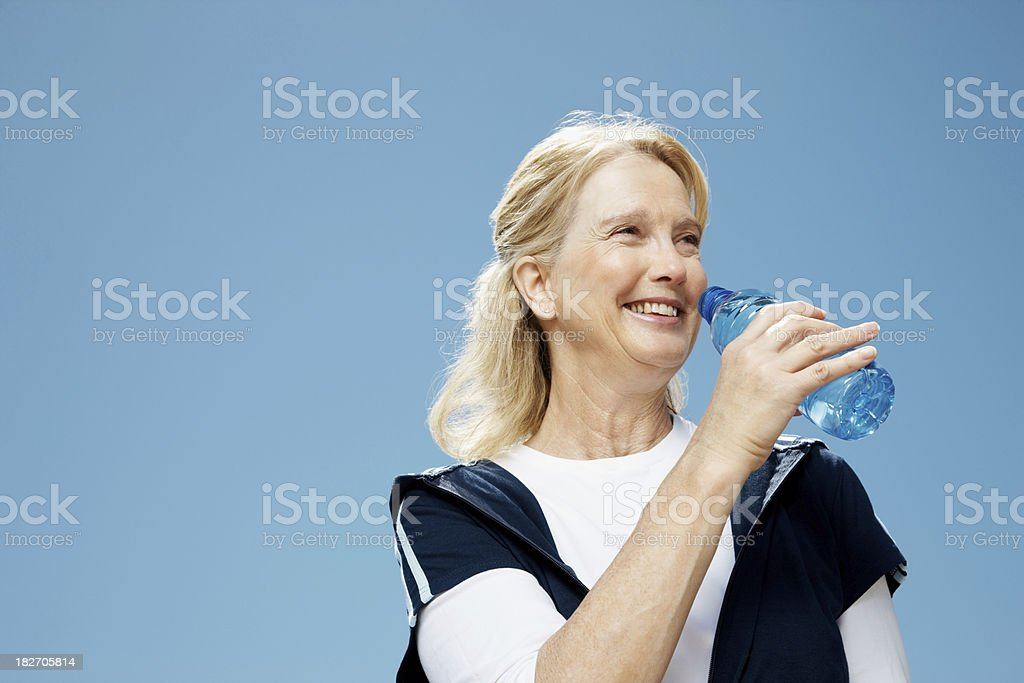 Happy mature woman drinking water against the clear sky royalty-free stock photo