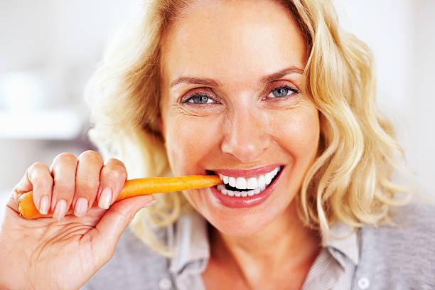 glückliche ältere frau isst a carrot-englische redewendung - karotten gesund stock-fotos und bilder