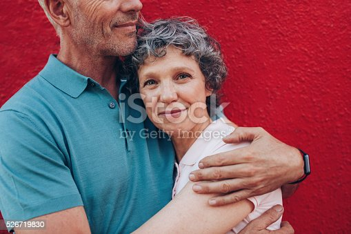529076288 istock photo Happy mature woman embracing her husband 526719830