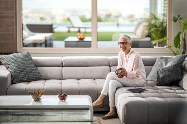 glücklich reife frau in ihrer kaffeezeit im wohnzimmer genießen. - seniorenwohnungen stock-fotos und bilder