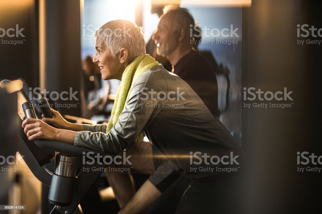 Happy mature woman feeling determined on spinning class in a gym. stock photo