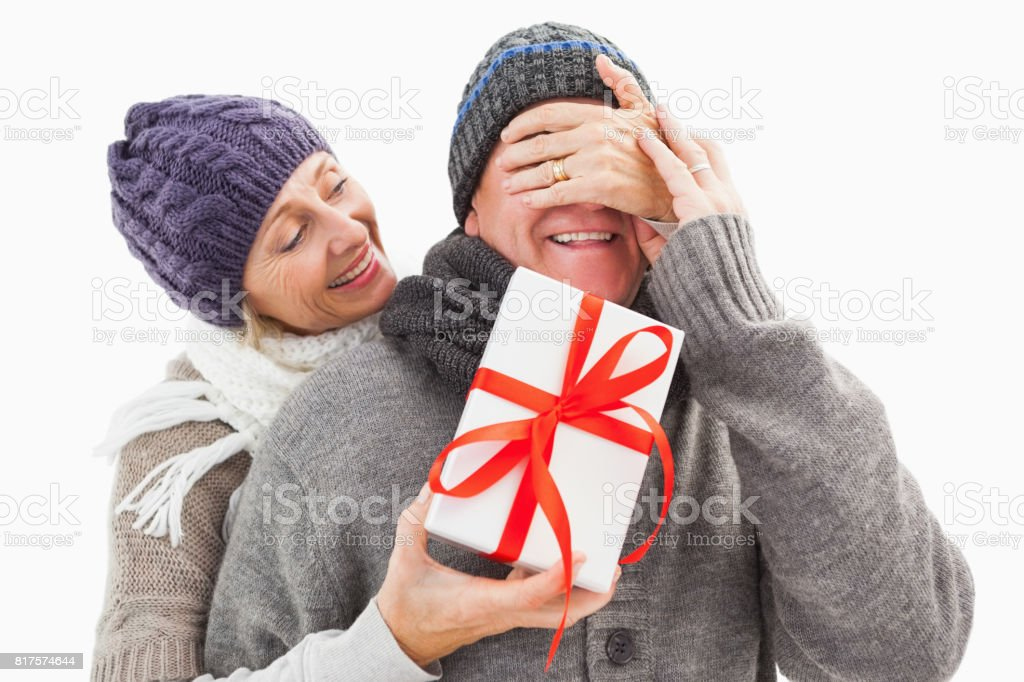 Happy mature woman hiding gift from partner stock photo
