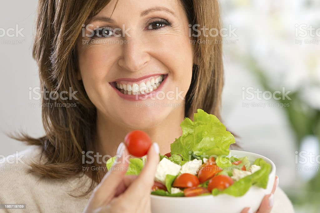 Happy mature woman holding a salad royalty-free stock photo
