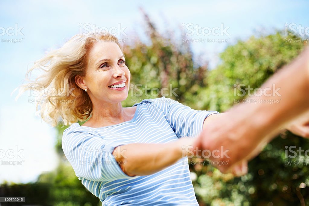 Happy mature woman holding hand's of a man - outdoor royalty-free stock photo