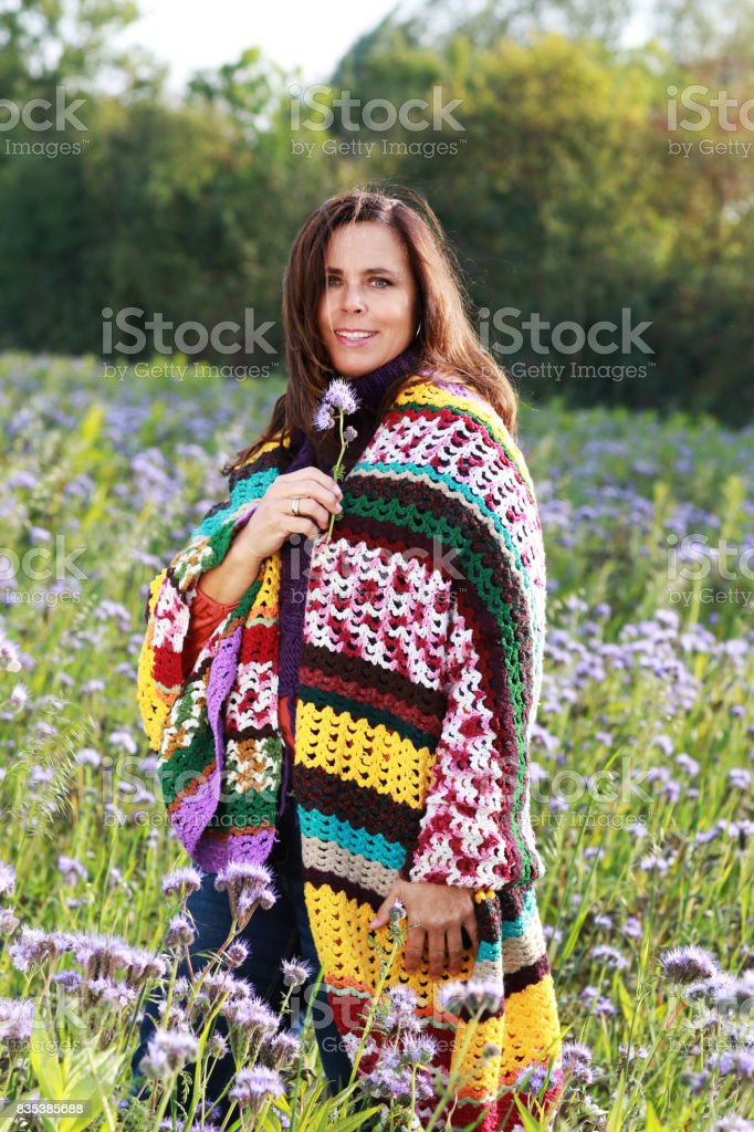 Happy mature woman in flower field enjoys life stock photo
