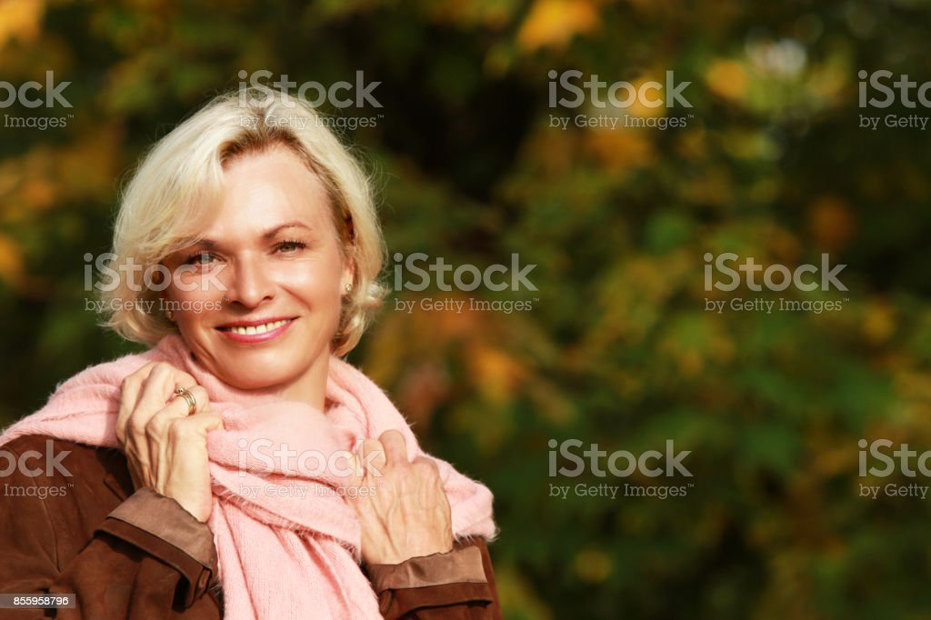 Happy Mature Woman In Front Of Golden Autumn Leaves Stock