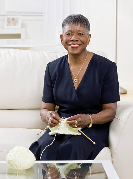 Happy Mature Woman Knitting On Couch stock photo