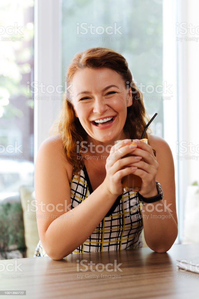 Happy woman. Happy mature woman laughing out loud while communicating...