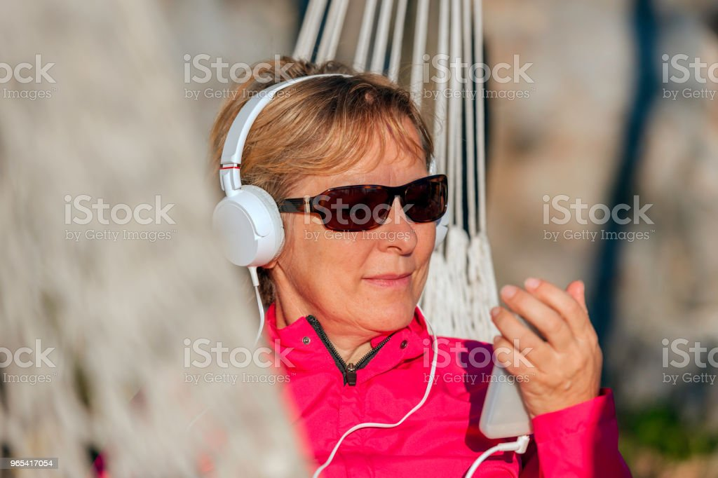 Happy Mature Woman Listening to Music on Hammock at Sunset,Italy,Europe royalty-free stock photo