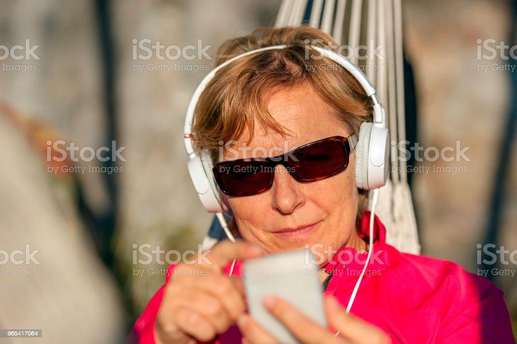 Happy Mature Woman Listening to Music on Hammock at Sunset,Italy,Europe - Zbiór zdjęć royalty-free (Brązowe włosy)