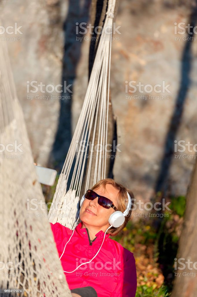 Happy Mature Woman Listening to Music on Hammock at Sunset,Italy,Europe zbiór zdjęć royalty-free