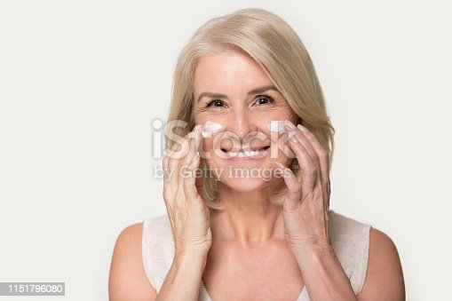 istock Happy mature woman looking at camera applying anti-aging cream 1151796080