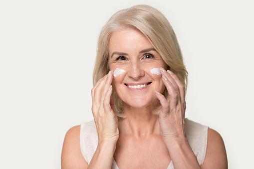 istock Happy mature woman looking at camera applying anti-aging cream 1151796080