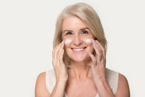 Happy mature woman looking at camera applying anti-aging cream Head shot studio portrait attractive mature blond woman look at camera gently touch face apply moisturizing or anti-aging wrinkle serum cream, natural beauty skin care concept image on grey background antiaging stock pictures, royalty-free photos & images