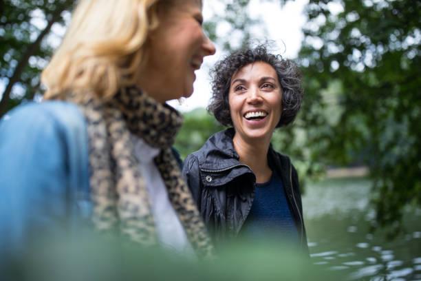 szczęśliwa dojrzała kobieta patrząca na przyjaciela w lesie - dwie osoby zdjęcia i obrazy z banku zdjęć