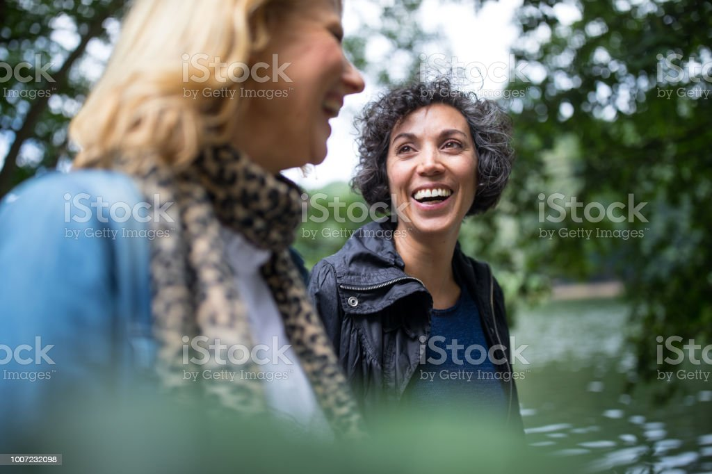 Happy mature woman looking at friend in forest stock photo