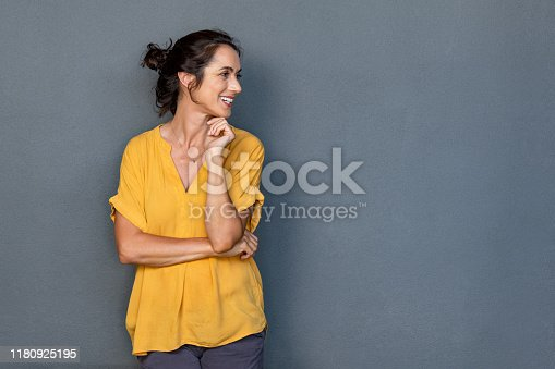 Mature beautiful latin woman isolated on grey background looking on side with copy space. Portrait of positive brunette woman smiling and looking away. Happy middle aged lady standing against grey wall and thinking.