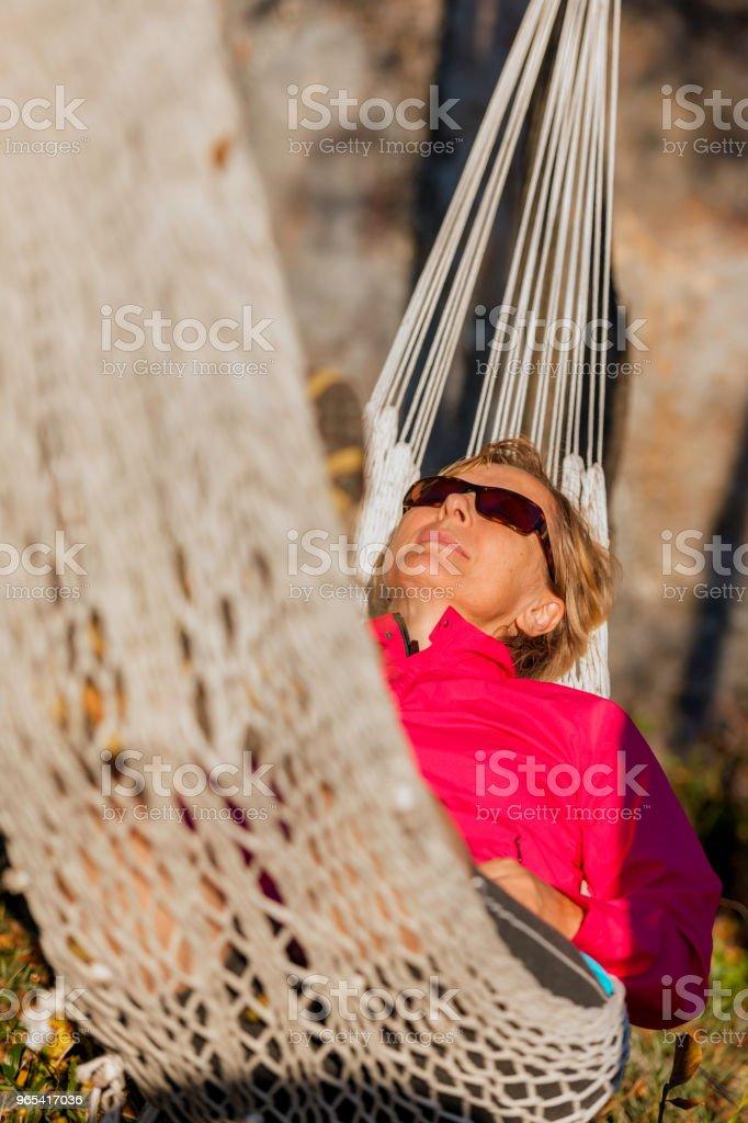 快樂成熟的女人躺在吊床上的荒野在日落, 義大利, 歐洲 - 免版稅一個人圖庫照片