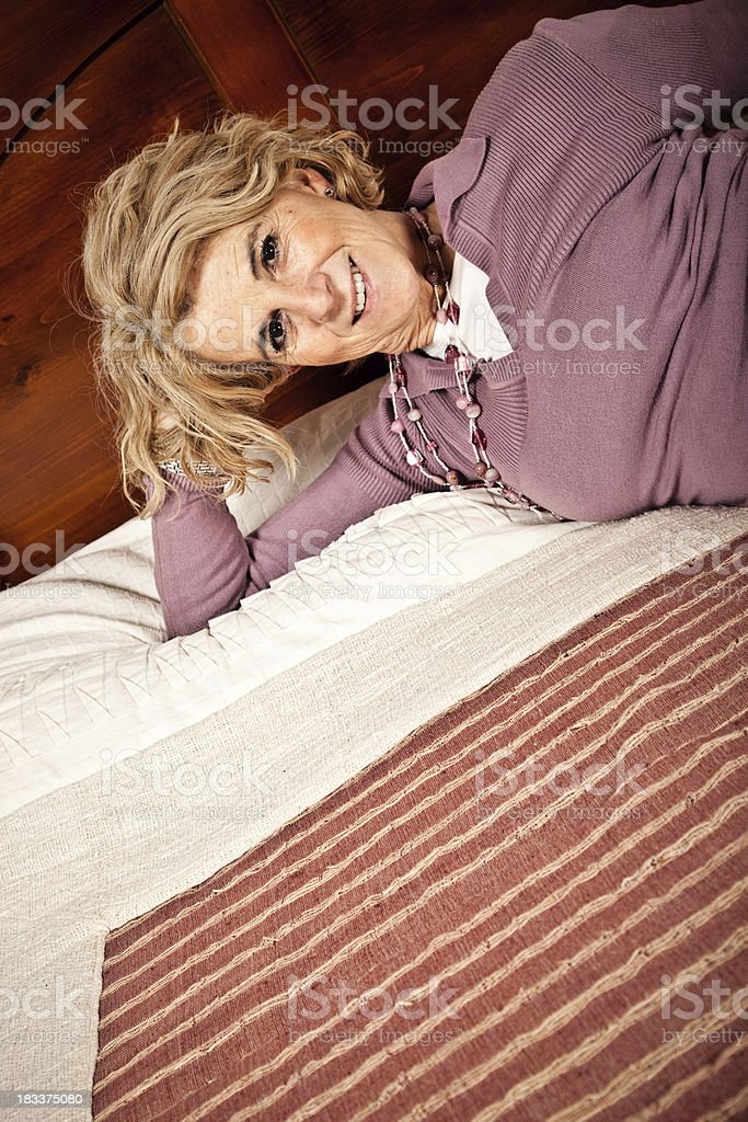 Happy Mature Woman Lying On The Bed royalty-free stock photo