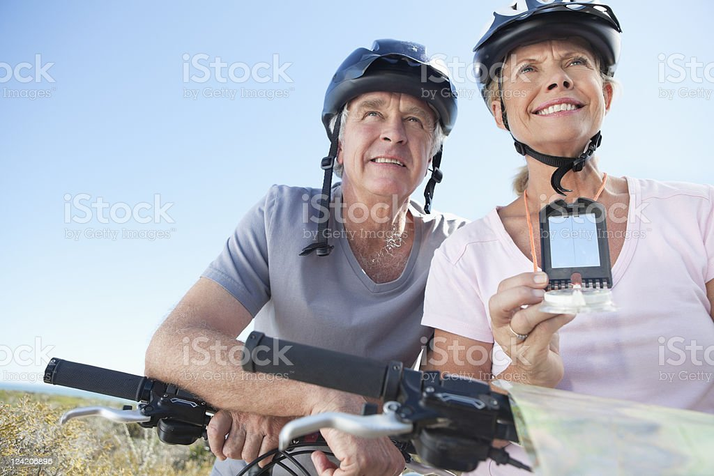 Happy mature woman mountain biking with man using GPS royalty-free stock photo