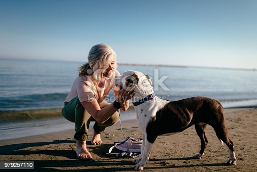 Happy active senior woman petting dog and relaxing by the sea in summer