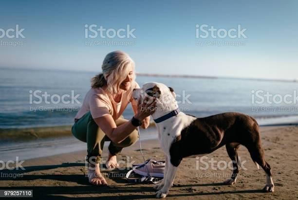 Happy mature woman petting dog on the beach in summer picture id979257110?b=1&k=6&m=979257110&s=612x612&h=ew4idoatlbgqkyhqzuprqar1tgd9lo7wapqaerb9f2w=