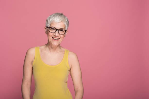 lycklig mogen kvinna - mature women studio grey hair bildbanksfoton och bilder