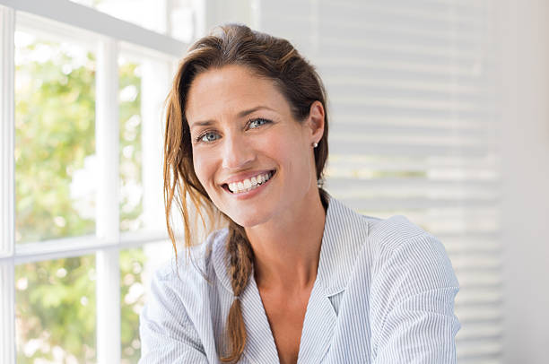 Happy mature woman Portrait of beautiful mature woman sitting and smiling. Woman feeling fresh on a bright sunny morning at home. Woman sitting in nightwear near the window and looking at camera. 30 34 years stock pictures, royalty-free photos & images