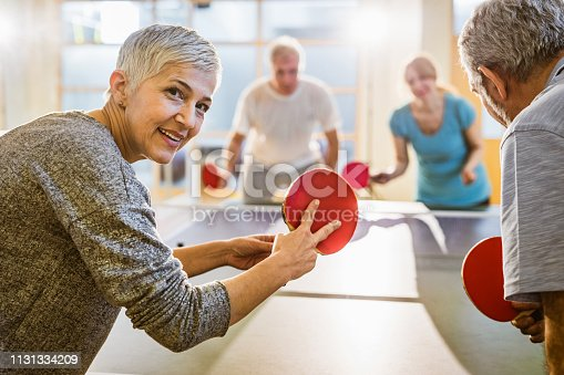 Smiling senior woman serving while playing table tennis with group of friends and looking at camera.