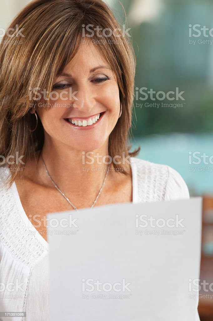 Happy mature woman reading a document royalty-free stock photo