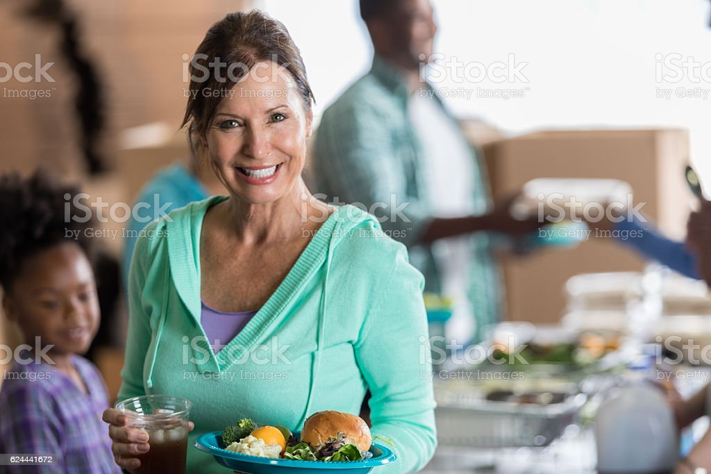 Cheerful mature Caucasian woman holds a plate of healthy food and...