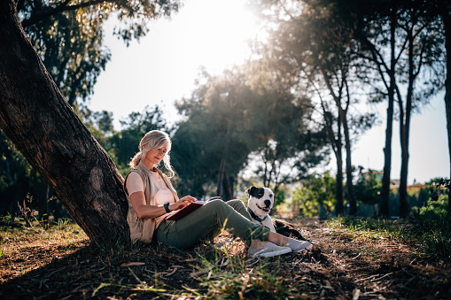 Happy mature woman relaxing in nature with dog and book