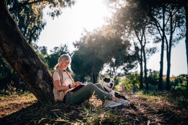 Mutlu olgun kadın köpek ve kitap ile doğada rahatlatıcı stok fotoğrafı