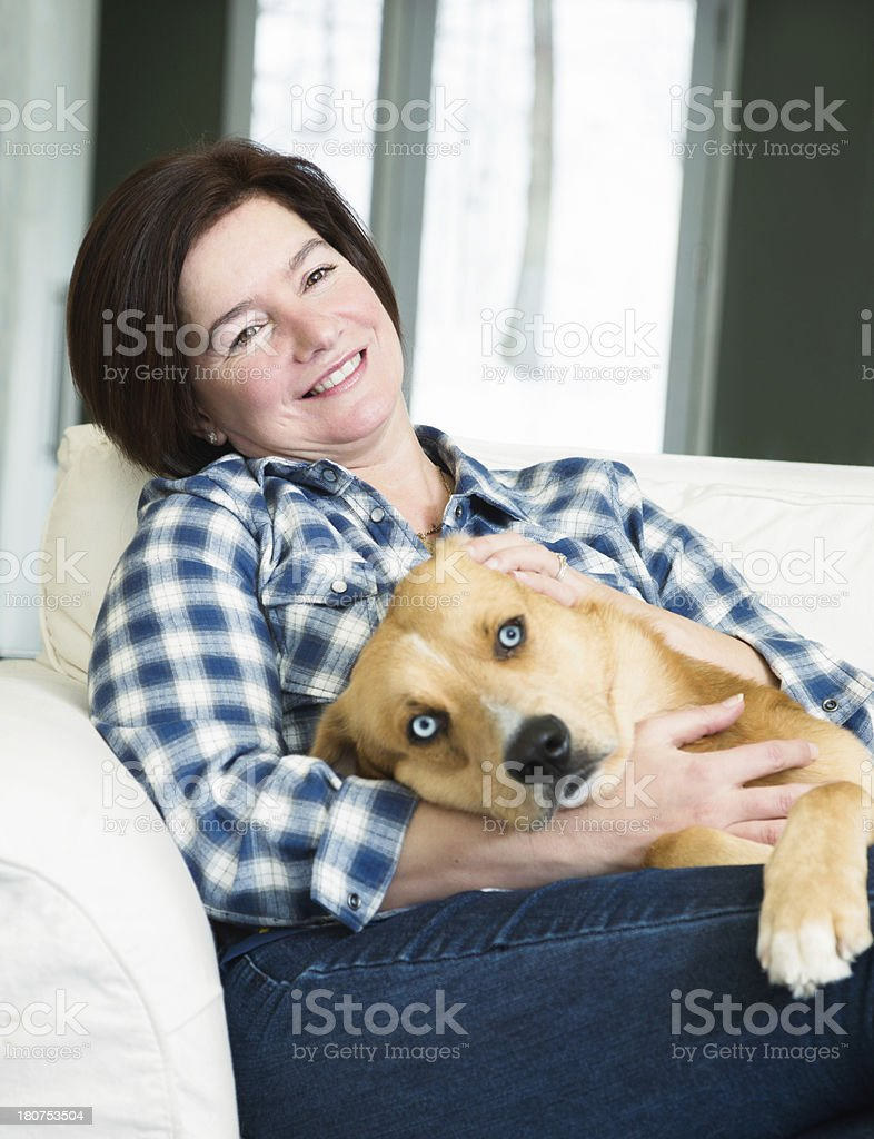 Happy mature woman relaxing with her dog royalty-free stock photo