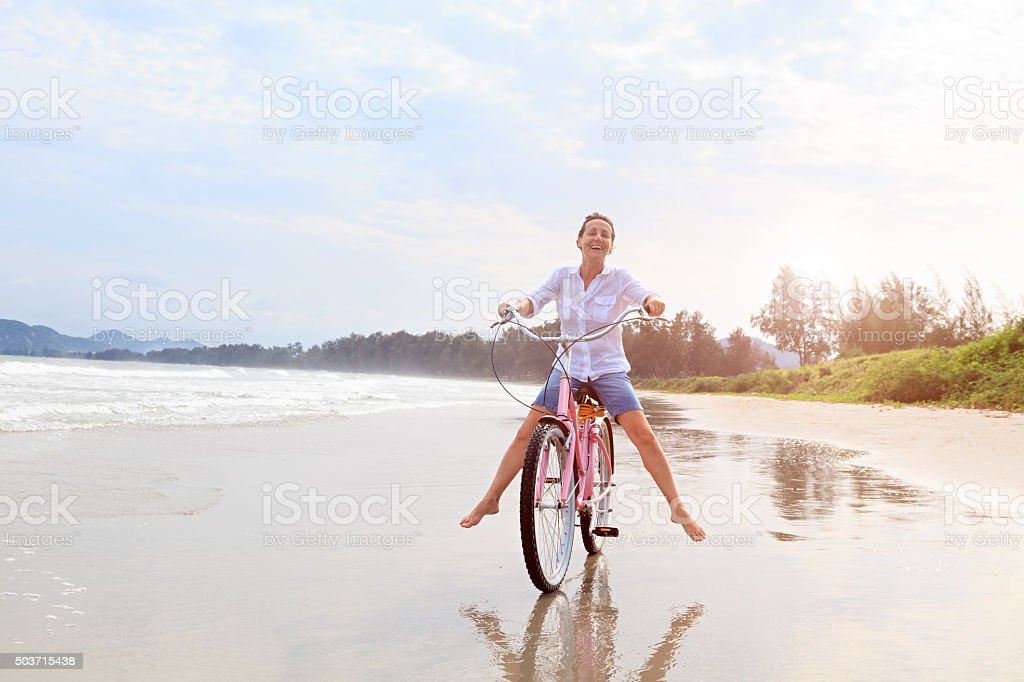 Happy mature woman riding bike on beach stock photo