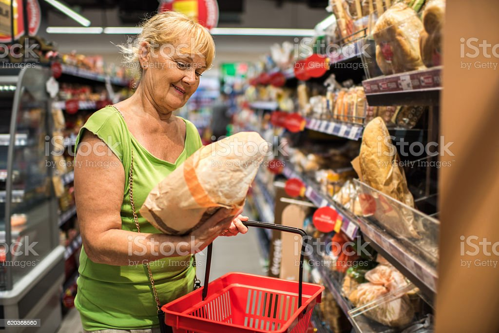 Happy mature woman shopping for bread in a store. zbiór zdjęć royalty-free
