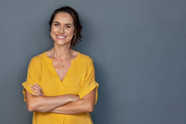 快樂成熟的女人在灰色的牆壁上微笑 - 女性 個照片及圖片檔