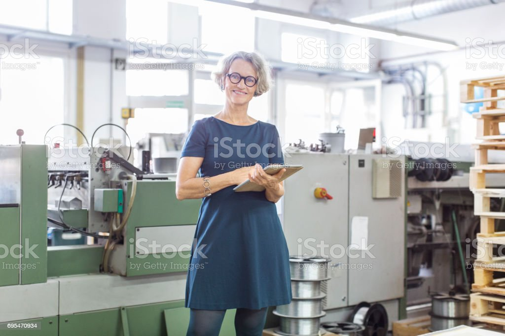 Happy mature woman standing by a printing machine stock photo