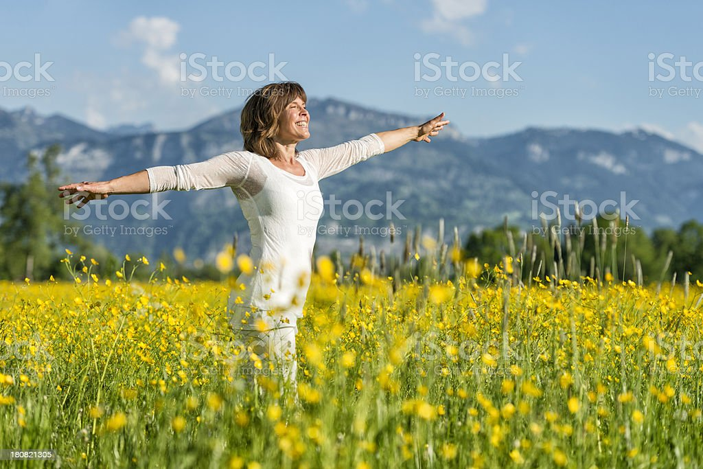 happy mature woman standing in flower meadow stock photo